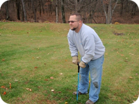 Probing the ground to locate a septic system's drain field.