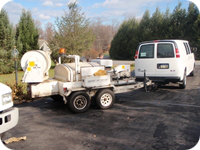 Trailer-mounted jets are used to clean septic drain field laterals.